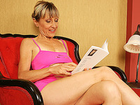 Blonde mature bitch in pink underwear is posing on the large bed